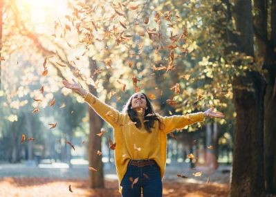 Woman-tossing-leaves-in-the-air-in-the-sunlight